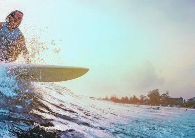 Surferridestheoceanwaveduringsunset.Extremesportandactivelifestyleconcept